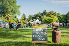 Weekend Farmers Market sign with groups of people sitting around Royalty Free Stock Photo
