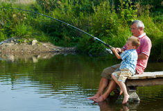 Weekend fishing. Photo of grandfather and grandson sitting on pontoon with their feet in water and fishing on weekend Royalty Free Stock Photo