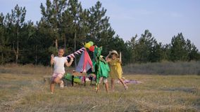 Weekend games in forest, active kids running around in a clearing decorated with wigwam catch each other in dragon