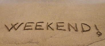 Weekend! geschreven in zand, op een mooi strand Stock Afbeelding