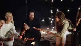Weekend, gli amici si siedono dalle salsiccie della torrefazione e del fuoco con le bevande alcoliche su fondo delle lampade dell