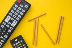TV inscription and remote controls. Weekend, hobby and leisure concept. A TV inscription made of bread sticks and remote controls on a bright one-colore yellow Royalty Free Stock Photos