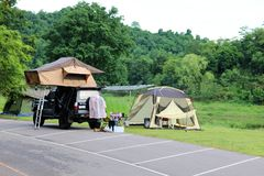 Weekend holiday in campsite and tents on the lawn and car park w. Ith beautiful green nature landscapes of dam water, forests, and mountains in Thailand stock photography