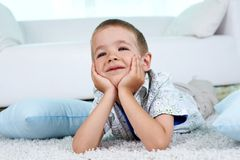 Weekend at home. Adorable child lying on the floor at home on weekend Royalty Free Stock Photo