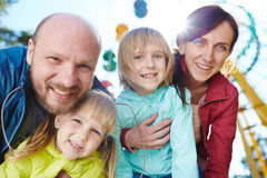 Weekend with Kids in Amusement Park. Portrait of happy family looking at camera bending down, parents hugging two beautiful daughters close in sunlight during Stock Photography
