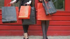 Weekend l'acquisto, amiche con i sacchi di carta in mani riposano dopo i riusciti acquisti video d archivio