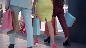 Weekend l'acquisto, ragazze alla moda in vestiti variopinti sulla camminata a tacco alto vicino ai depositi in centro commerciale stock footage