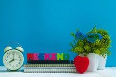 WEEKEND las letras mandan un SMS y el papel del cuaderno, despertador y poco imagen de archivo libre de regalías