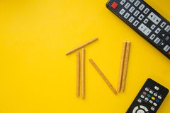 TV inscription and remote controls. Weekend, leisure and hobby concept. A TV inscription made of bread sticks and remote controls on a bright one-colore yellow Stock Photography