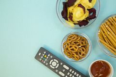 Watching TV concept. Weekend, Leisure, Lifestyle Concept. Evening in front of tv with a remote control, pretzels, chips and bread sticks on a light blue Stock Photos