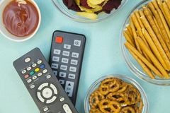 Watching TV concept. Weekend, Leisure, Lifestyle Concept. Evening in front of tv with two remote controls, pretzels, chips and bread sticks on a light blue Stock Image