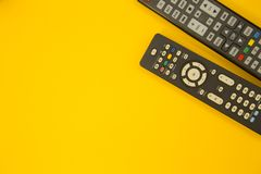 Watching TV concept. Weekend, Leisure, Lifestyle Concept with two TV remote controls on a bright one-colore yellow background, flat lay Stock Photos