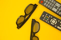 Watching TV concept. Weekend, Leisure, Lifestyle Concept with two TV remote controls, two pairs of 3d glasses on a bright one-colore yellow background, flat lay Stock Images