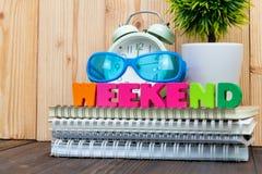 WEEKEND letras text e papel do caderno, despertador e pouco fotografia de stock royalty free