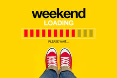 Weekend Loading Concept. Weekend Loading Content with Young Person Wearing Red Sneakers from Above Standing in front of Loading Progress Bar, waiting for the End Stock Photo