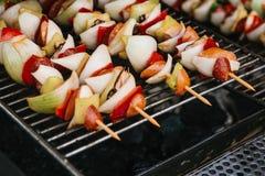 weekend Los pinchos con los pedazos de salchichas, cebollas, pimientas se cocinan en una rejilla en los carbones Resto y consumic fotos de archivo libres de regalías