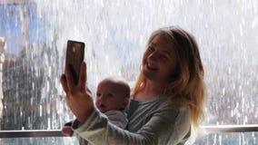 Weekend, madre joven con el bebé en los brazos que hacen la foto del selfie usando el teléfono móvil en el fondo de la pared del  almacen de metraje de vídeo