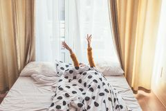 Weekend morning in hotel. Girl stretching in bed in hotel room infront of big window. Lazy weekend morning concept stock photos