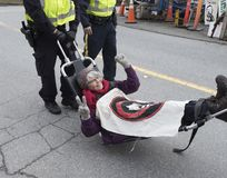 Protesters at the Kinder Morgan tank farm in Burnaby, BC April, 2018. A woman is arrested at the Kinder Morgan tank farm in Burnaby BC while protesting the stock photos