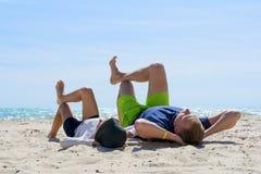 Weekend przy plażą Tata i syn kłamamy na plaży Tata i syn relaksuje na plaży obrazy royalty free
