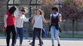Weekend, ragazze delle nazionalità differenti che ballano tenersi per mano e che si divertono all'aperto al rallentatore stock footage