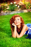 Weekend. Romantic young woman lying on a green lawn at a park. Summer day Royalty Free Stock Image