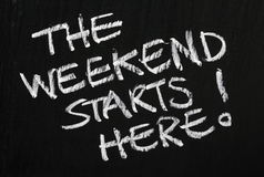 The Weekend Starts Here!. The phrase The Weekend Starts Here! written in white chalk on a used blackboard Royalty Free Stock Photos