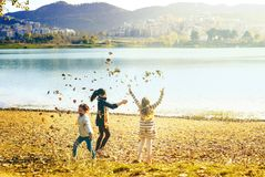 Weekend in Tirana at the lake. Tirana, Albania. November 5, 2017: Tirana Grand Park and Artificial lake shore, girls playing with autumn leaves throwing them in Royalty Free Stock Photos