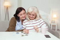 Optimistic elder woman and caregiver assembling puzzle. Weekend together. Joyful elder women and caregiver embracing while gathering puzzle stock images