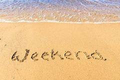 Weekend written on sand. Sandy beach with Weekend sign scribbled on beach sand. leisure time concept stock photo
