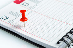 Weekly agenda with spiral and pin. On a white table Royalty Free Stock Image