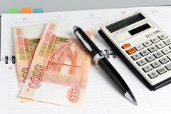 Weekly, black pen, calculator and money closeup Royalty Free Stock Image