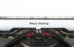 Weekly Briefing. An old typewriter still going with the words Weekly Briefing just been typed. Copyspace Royalty Free Stock Photo