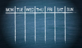 Weekly calendar. Illustration of a weekly calendar drawn on a black (part blue) chalkboard with seven columns and one row at the top starting on Monday then