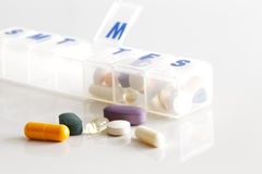 A weekly container of tablets, vitamins etc. On white reflective ceramic surface Stock Photography