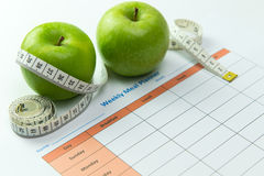 Weekly meal planner. With green apples and tape measurement Royalty Free Stock Photo