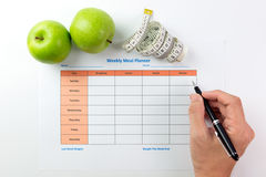Weekly meal planner. Weekly meal planning sheet with green apples, tape measurement and pen Stock Images