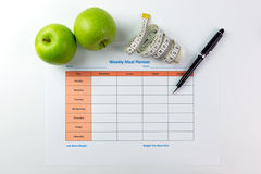 Weekly meal planner. Weekly meal planning sheet with green apples, tape measurement and pen Royalty Free Stock Image
