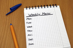 Weekly Menu. Words Weekly Menu written on white note pad with ballpoint pen Stock Images