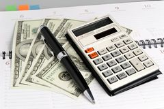 Weekly with pen, calculator and dollars closeup Royalty Free Stock Photo