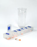 Weekly pill box with glass of water. Weekly pill box with pills and glass of water Stock Photo