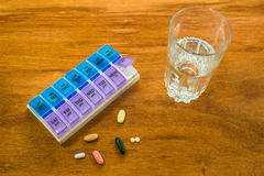 Weekly Pill Box & Glass Of Water Stock Images