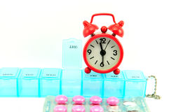 Weekly pill box and red clock on white blackground. Show medicine concept Stock Photo
