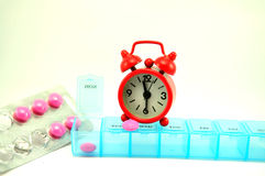 Weekly pill box and red clock on white blackground. Show medicine time Royalty Free Stock Image