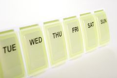Weekly Pill Organizer. Close up of weekly pill organizer with days of the week printed on front Stock Image
