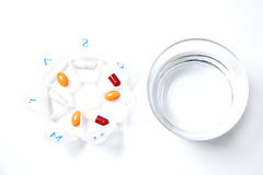 Take the pills. A weekly pillbox by a water glass. An aerial point of view Stock Photo