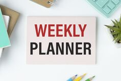WEEKLY PLANNER on notepad. Business concept with office tools on chart background