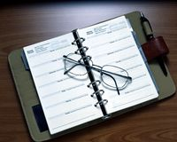 Weekly Planner. An open weekly planner and eye glasses on a table Stock Photo