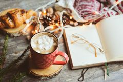 Weekly planner or to do list top view with Christmas decorations and hot cocoa. Choosing gifts and planning holidays concept Stock Photos