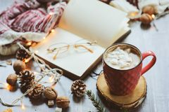 Weekly planner or to do list top view with Christmas decorations and hot cocoa. Choosing gifts and planning holidays concept Royalty Free Stock Photography